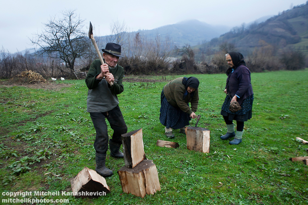Rural Romanian elders chopping wood. Maramures, Romania