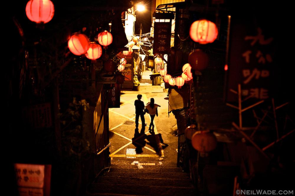 After dark, a couple strolls through Jioufen, in Rueifang Township, Taiwan.
