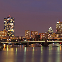 Boston skyline night photography showing landmarks such as John Hancock building, Prudential Center, and Longfellow Bridge captured on an overcast day in December at twilight.<br />