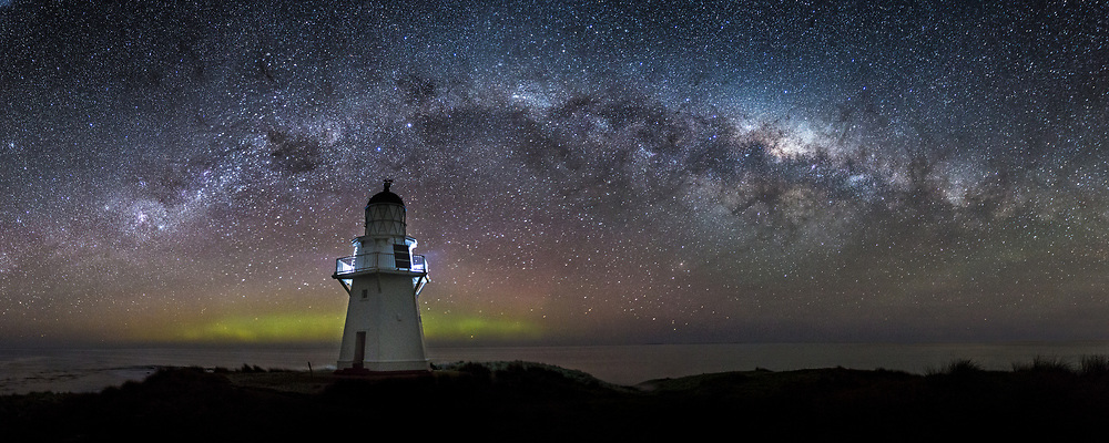 22x55 inch panoramic print.  A faint Aurora glows behind the Waipapa Point Lighthouse, as the Milky Way arcs overhead.  Catlins, South Island, New Zealand.  September 2nd, 2013.
