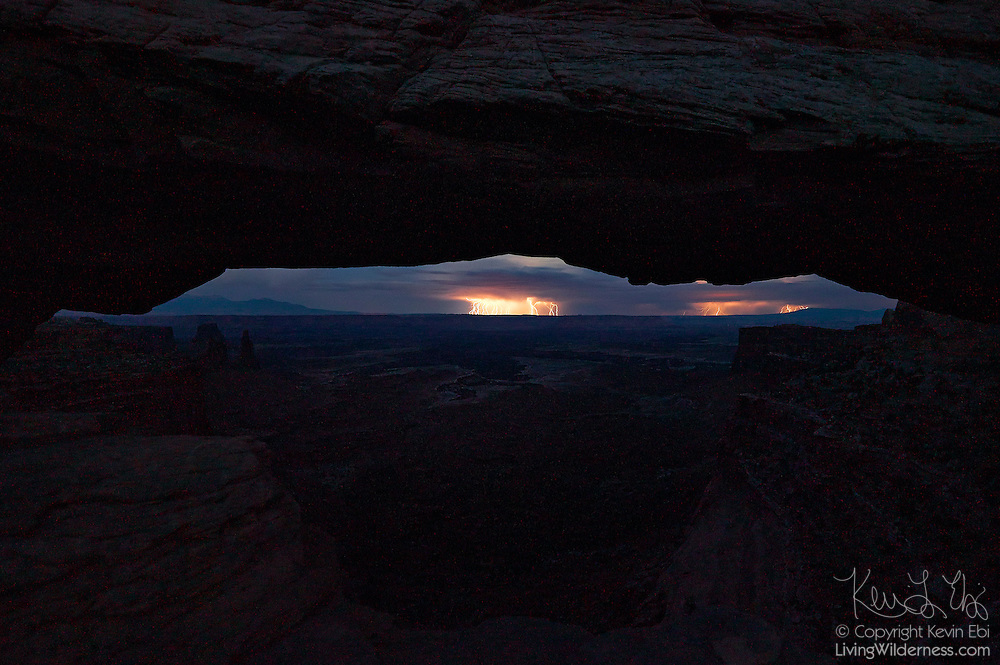 A 10-minute exposure captures a nighttime lightning storm, visible through Mesa Arch in Canyonlands National Park, Utah.