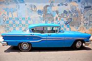 Old blue American car in front of blue wall art in Havana, Cuba.