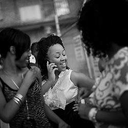 From left, Tyonna Foster, 18 laughs as her sister Michelle Henderson, 17, talks on the phone and sister Monaye Scott, 16 (in pink) looks on outside their apartment building in South East Washington, D.C. The sisters lost their father to street violence several years before and since have been taking care of each other. They started a singing group and wrote a tribute song about their father's death that they sang at the peace rally.