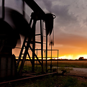 Oil Pump Jack under stormy sky at sunset.Rural Augusta, Butler County,  KS.May 19, 2012