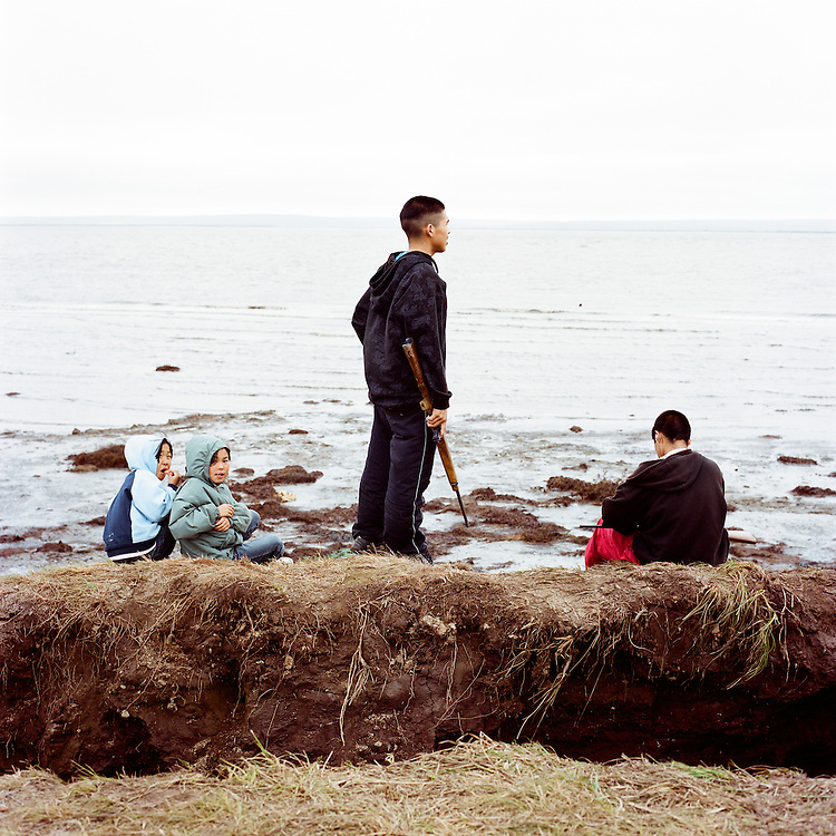 NEWTOK, ALASKA - 2008: Hanna, Sabrina, Bosco and Bosco playing on coastal erosion.