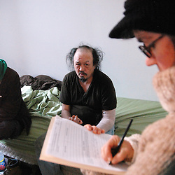 """IPTC Caption:USA, IL, Chicago, December 28, 2010.  Working in tandem, social worker Anne Leto from Health & Disability Advocates and Eric Swiecki from Thresholds assess the needs of """"Jesse,"""" off the winter streets of Chicago for the first time in  twenty years. HDA is one of the only agencies entitled to provide """"presumptive benefits"""" to candidates in serious trouble, enabling them to begin immediate assistance while paperwork is completed. Homeless people are often unable to provide the documentation they need for any kind of service. In a process that began more than a year ago, Thresholds staff were able to finally determine """"Jesse's"""" identity. One of their mental health teams will now monitor his gradual re-entry into society, while HDA, which unites legal and health experts, will ensure his benefits are administered."""