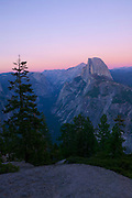A colorful fall sunset colors the sky over Half Dome and the glacier-carved Yosemite Valley. The Earth's shadow is visible at the horizon. Geologists now think the missing piece is more like a quarter of the dome than half.