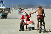 A woman gives some gatorade to a man dressed as Santa Claus as she rides past him in the playa at Burning Man in the Black Rock Desert in Nevada.