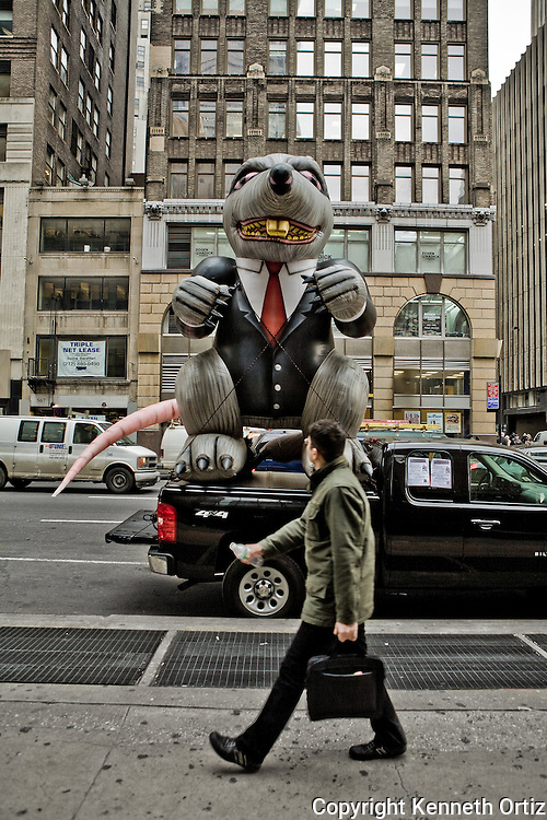 Picture of a young man walking up 7th Avenue pasta Rat balloon, dressed in a business suit.