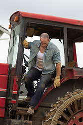 male farmer getting down from a tractor
