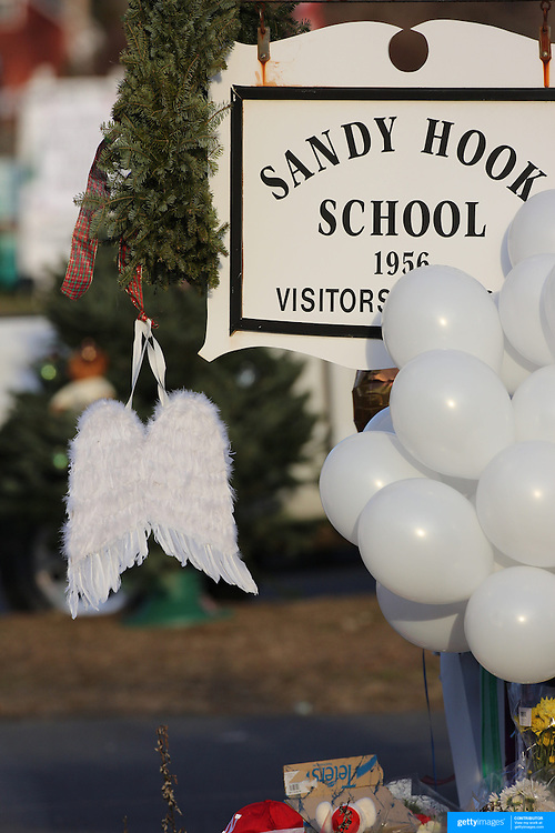 Angel wings hang from the school sign where a shrine created under the school sign in Sandy Hook after yesterday's shootings at Sandy Hook Elementary School, Newtown, Connecticut, USA. 15th December 2012. Photo Tim Clayton