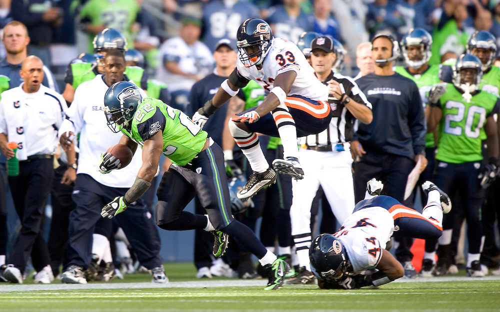 SEATTLE SEAHAWKS VS CHICAGO BEARS - As Seattle's Julius Jones heads up the Seahawks sideline, Chicago's Charles Tillman leapfrogs teammate Kevin Payne in an attempt to make the tackle.
