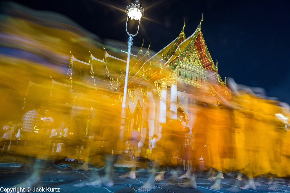 """25 FEBRUARY 2013 - BANGKOK, THAILAND:  Buddhist monks lead a candle light procession around Wat Benchamabophit Dusitvanaram (popularly known as either Wat Bencha or the Marble Temple) on Makha Bucha Day. Thais visit temples throughout the Kingdom on Makha Bucha Day to make merit and participate in candle light processions around the temples. Makha Bucha is a Buddhist holiday celebrated in Myanmar (Burma), Thailand, Cambodia and Laos on the full moon day of the third lunar month (February 25 in 2013). The third lunar month is known in Thai is Makha. Bucha is a Thai word meaning """"to venerate"""" or """"to honor"""". Makha Bucha Day is for the veneration of Buddha and his teachings on the full moon day of the third lunar month. Makha Bucha Day marks the day that 1,250 Arahata spontaneously came to see the Buddha. The Buddha in turn laid down the principles his teachings. In Thailand, this teaching has been dubbed the 'Heart of Buddhism'.     PHOTO BY JACK KURTZ"""