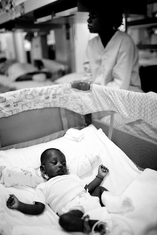 A two-month-old Haitian boy sleeps in a crib after a television fell on his foot and injured it during the earthquake as his mother looks on in the pediatric ward on board the USNS Comfort, a U.S. Naval hospital ship, on January 21, 2010 in Port-au-Prince, Haiti. The Comfort deployed from Baltimore with 550 medical personnel on board to treat victims of Haiti's recent earthquake, and arrived on January 20.