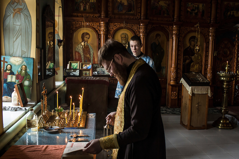 Priest Rostislav Morozov, left, leads parishoners in a service at the Church of Our Lady of Kazan on Sunday, February 14, 2016 in Pervomaiske, Ukraine.