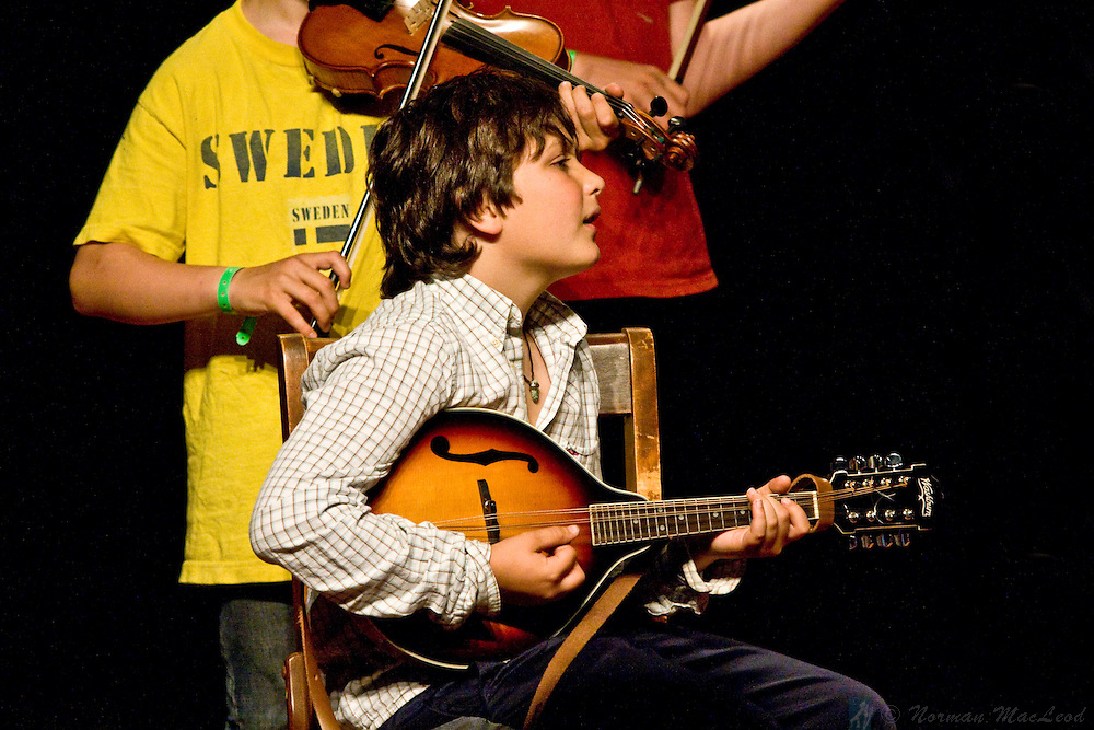 Young mandolin player onstage with Andy Mackie at the Festival of American Fiddle Tunes participants' concert