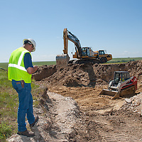 surveyor at wind tower base on wind project site