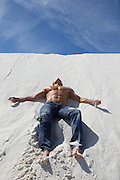 man without a shirt resting on a sand dune in White Sands, NM