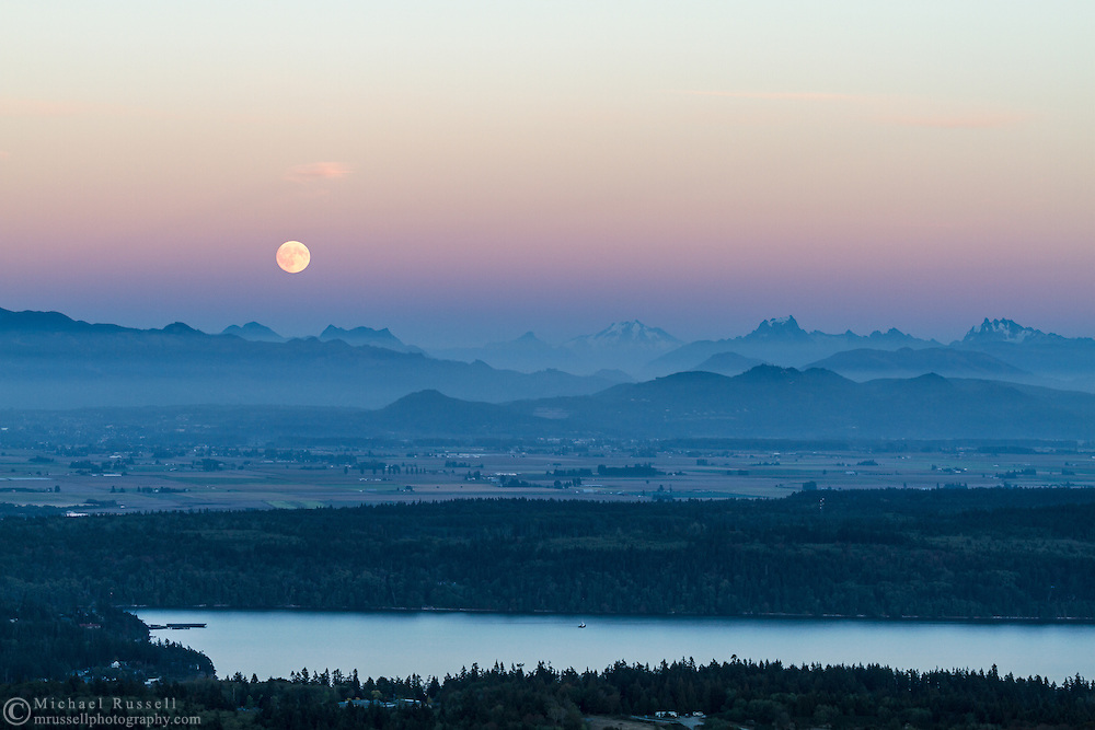 The moon rises above Earth's Shadow over the peaks of the North Cascades mountains in Washington State, USA.  Peaks here include (L to R) Round Mountain, Mount Higgins, Skadulgwas Peak, White Chuck Mountain, Glacier Peak, Disappointment Peak and Whitehorse Mountain.  Similk Bay is in the foreground. Photographed from Mt. Erie Park on Fidalgo Island, Washington.