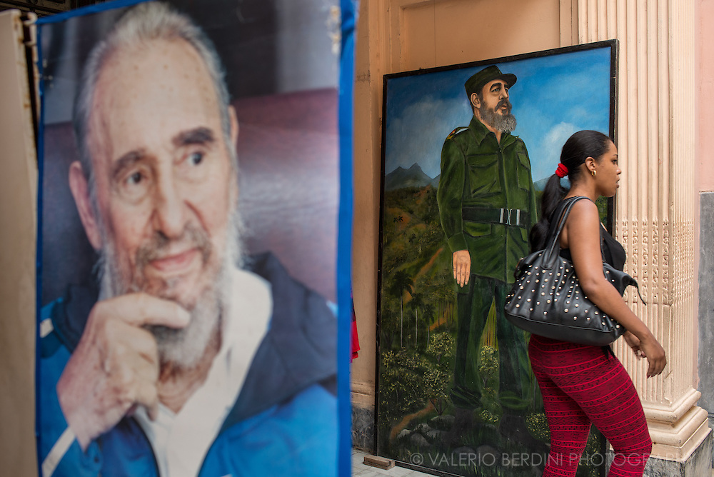 A woman passes by two pictures of Fidel Castro in Old Havana. Cuba, 2015.