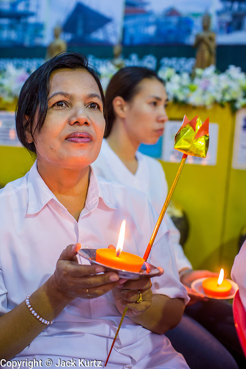 23 OCTOBER 2012 - HAT YAI, SONGKHLA, THAILAND:  A woman holds a candle during a service on the last day of the Vegetarian Festival at Wat Ta Won Vararum, a Chinese Buddhist temple in Hat Yai. The Vegetarian Festival is celebrated in Thai-Chinese communities throughout Thailand. It is the Thai Buddhist version of the The Nine Emperor Gods Festival, a nine-day Taoist celebration celebrated in the 9th lunar month of the Chinese calendar. For nine days, those who are participating in the festival dress all in white and abstain from eating meat, poultry, seafood, and dairy products. Vendors and proprietors of restaurants indicate that vegetarian food is for sale at their establishments by putting a yellow flag out with Thai characters for meatless written on it in red.  PHOTO BY JACK KURTZ