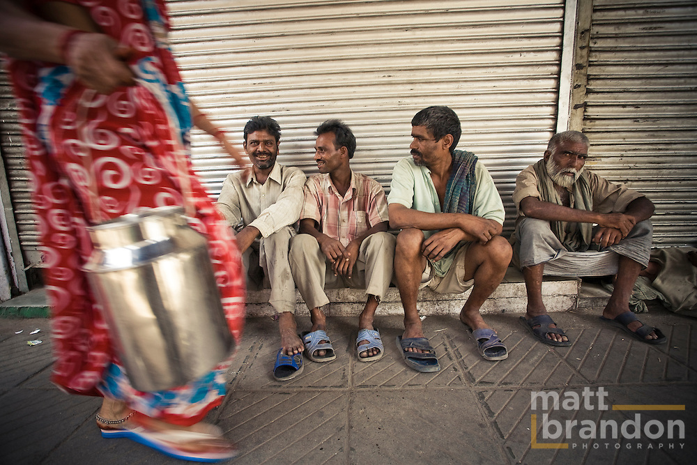 Day labors sit watching life pass by them as they wait for work. Old Delhi, India.