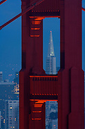 A dusk view of San Francisco with the Transamerica building through the Golden Gate Bridge.