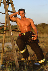 shirtless hunky fireman leaning on a ladder outdoors