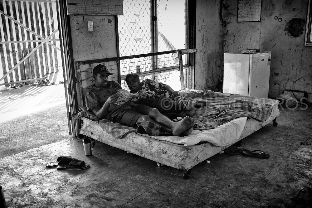 A couple reading a magazine in the old Office (now demolished) in the One Mile community. Some are in Broome to visit family, while others come to receive medical attention or escape wet season flooding. Broome has a lack of affordable short-term accommodation. Broome Western Australia.