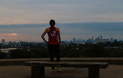 Primrose Hill, London, September 22nd 2016. A runner rests and admires the view from Primrose Hill as the autumn equinox sun rises over London . &copy;Paul Davey<br /> FOR LICENCING CONTACT: Paul Davey +44 (0) 7966 016 296 paul@pauldaveycreative.co.uk