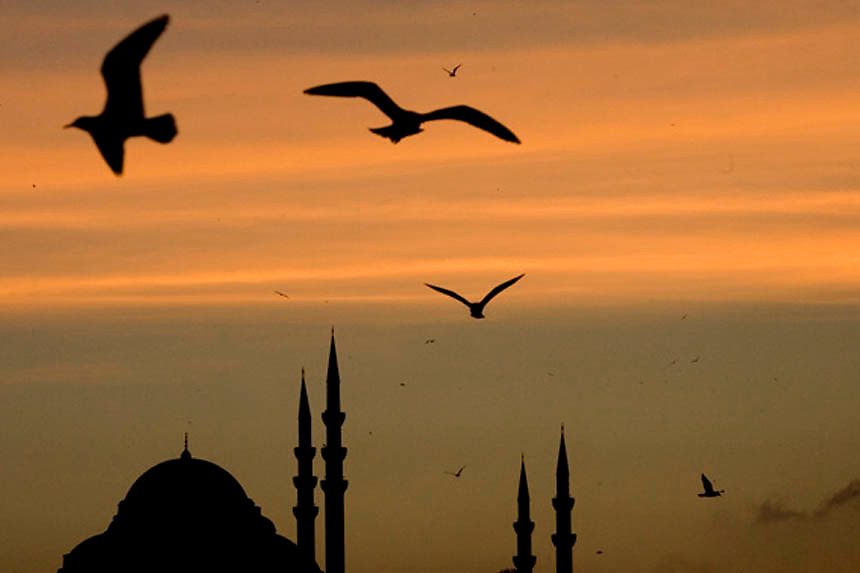 A mosquee is silhouetted at sunset in downtown Istanbul