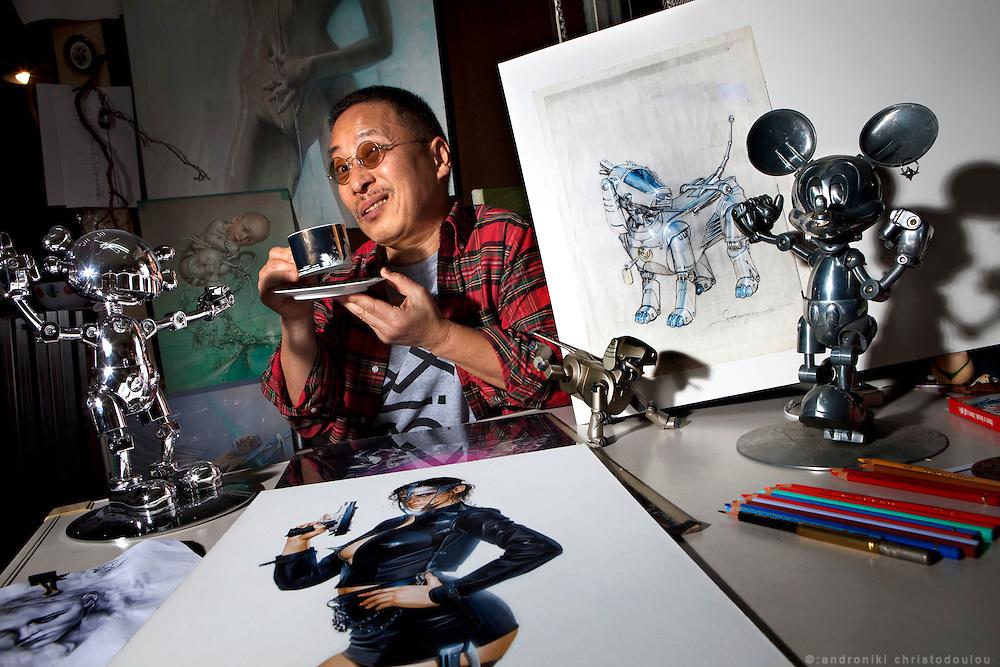 "Japanese artist Hajime Sorayama in his studio, surrounded by the original design of ibot, his drawings and KAWS x Hajime Sorayama Collaboration - ""No Future Companion"" silver figure (left) and Mickey (Right)"