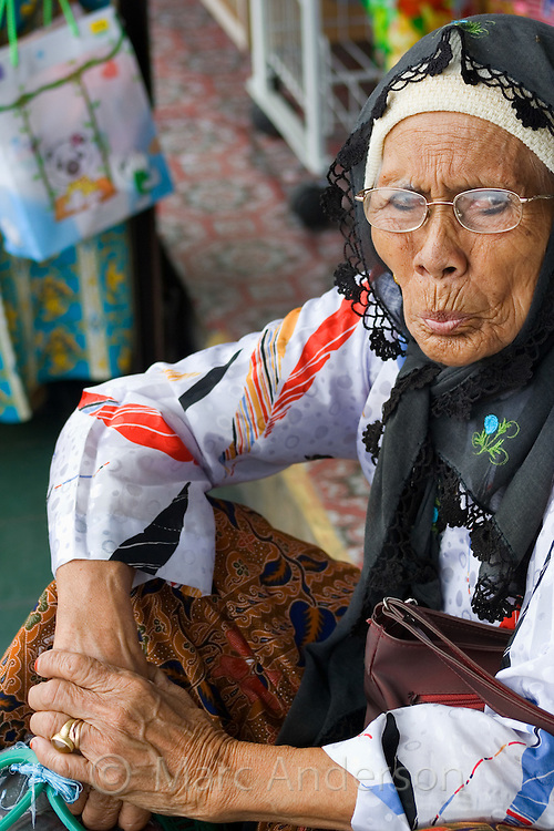 An old Malaysian woman sitting on the street..