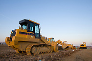A tracked loader and several other pieces of construction machinery rest in a muddy field near Joliet, IL.