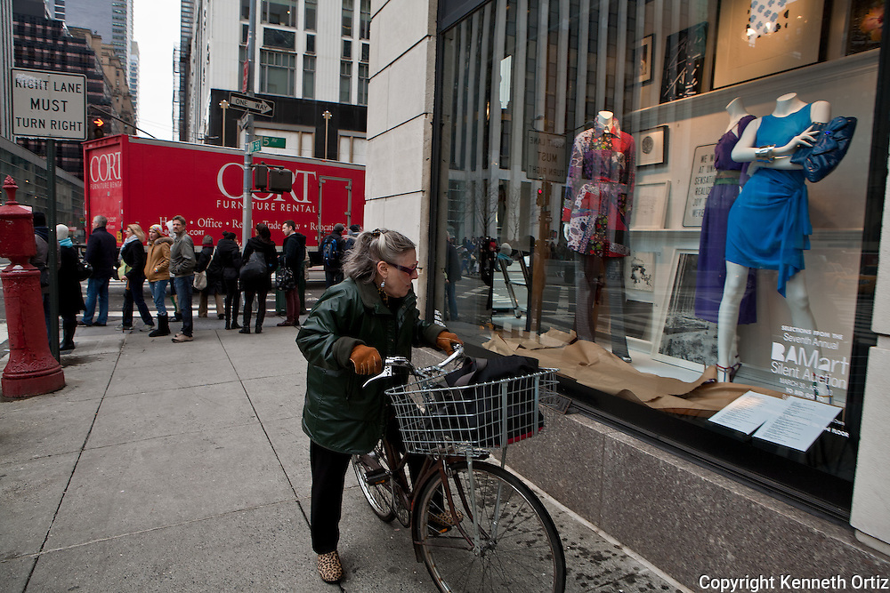A female bicyclist checking out the latest fashion at Bergdorf Goodmans.