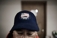 """OHIO, Toledo, October 27, 2012:  A volunteer standing with the blue baseball hat with the word """"freedom"""" inside the """"Primera Iglesia Bautista"""" where clothes and food is being distributed. ALESSIO ROMENZI"""