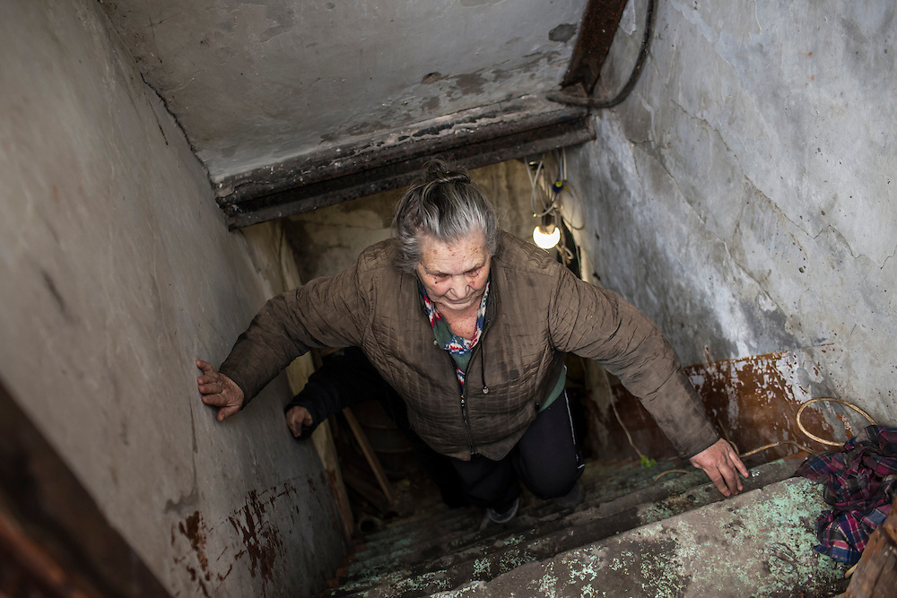 DONETSK, UKRAINE - FEBRUARY 3, 2015: Alla Kozikova, 81, climbs out of the basement shelter in which she and some of her neighbors have been living for days in the Petrovsky district of Donetsk, Ukraine. The neighborhood has been under heavy shelling for the past four days, and a brief pause allowed a few residents to leave their basement hiding places for some fresh air. CREDIT: Brendan Hoffman for The New York Times