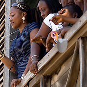 A woman stands in a top-floor window while filming the parade held on the occasion of the annual Oguaa Fetu Afahye Festival in Cape Coast, Ghana on Saturday September 6, 2008..