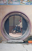 Masked women on a moped seen through a round door of Nghia An Hoi Quan Pagoda on 678 Nguyen Trai Street in Cholon, Ho Chi Minh City