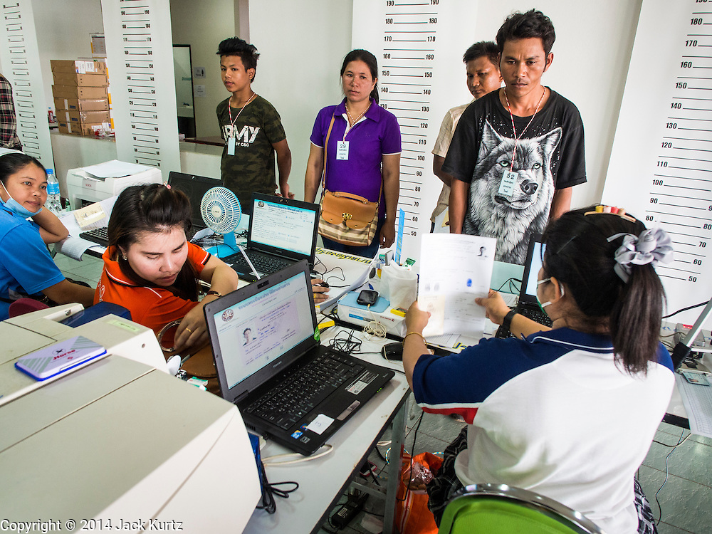 09 JULY 2014 - ARANYAPRATHET, SA KAEO, THAILAND: Cambodian migrant workers line up for photos and ID cards at the Thai Immigration One Stop Service Center in Aranyaprathet on the Thai-Cambodian border. More than 200,000 Cambodian migrant workers, most undocumented, fled Thailand in early June fearing a crackdown by Thai authorities after a coup unseated the elected government. Employers have been unable to fill the vacancies created by the Cambodian exodus and the Thai government has allowed them to return. The Cambodian workers have to have a job and their employers have to vouch for them. The Thai government is issuing temporary ID cards to allow them to travel openly to their jobs. About 800 Cambodian workers came back to Thailand through the Aranyaprathet border crossing Wednesday. The Thai government has opening similar service centers at three other crossing points on the Thai-Cambodian border.    PHOTO BY JACK KURTZ
