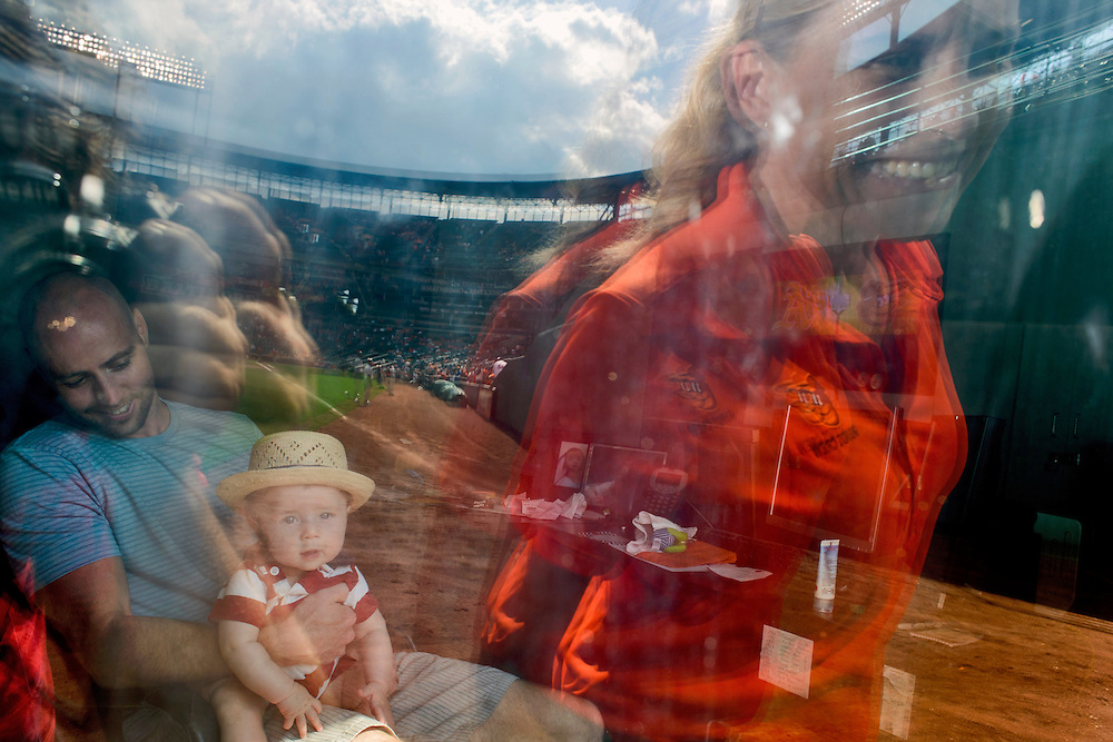 Photo by Matt Roth<br /> Assignment ID: 30146796A<br /> <br /> Nicole McFadyen, head groundskeeper for the Baltimore Orioles, makes a quick stop at a window along the right field wall to say hi to her husband Dan McFayden and their four-month-old son Tyson. Nicole readies Camden Yard's infield for the Oriole's game against the Oakland Athletics in Baltimore, Maryland on Saturday, August 24, 2013. McFayden, who's held her position for seven years, is one of two female head groundskeepers in the Major Leagues.