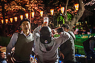 """Young man chugs some sort of flavored wine drink while his friends encourage him.  As the evening progress, things can get a little out of hand at o-hanami, """"flower-viewing"""", celebrations in Ueno Park.  Perhaps as a result, the lights in the park automatically go off at the early hour of 8pm.  Still, there is plenty of time for revellers to loosen up.  Ueno Park, Tokyo, Japan."""