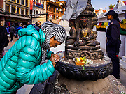 17 MARCH 2017 - KATHMANDU, NEPAL: A woman touches her forehead to a statue of the Buddha as a sign of piety during morning prayers at Boudhanath Stupa in Kathmandu. The stupa is the holiest site in Nepali Buddhism. It is also the center of the Tibetan exile community in Kathmandu. The Stupa was badly damaged in the 2015 earthquake but was one of the first buildings renovated.     PHOTO BY JACK KURTZ