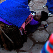 An injured villager, with severe bleeding from the back of the head is aided by a women after fighting in the streets of Macha during the Tinku Festival. Macha, Bolivia, 4th May 2010, Photo Tim Clayton ..Each May, up to 3000 thousands indigenous Bolivian indians descend on the isolated mountainous village of Macha 75 miles north of Potosi in the Bolivian Andes. The 600 year old pre-hispanic Bolivia Festival of Tinku sees villagers from all over the region march into town to be pitted against each other in a toe to toe fist to fist combat.. They dance and sing in traditional costume and drink 96% proof alcohol along with chicha, a fermented beverage made from corn. Townspeople and sometimes the police oversee proceedings who often use tear gas to try and control the villages, whipped into a fighting frenzy by the dancing and alcohol, but as the fiesta goes on things often escalate beyond their control, with pitched battles between rival villages break out,  The blood spilt is an offering to the earth goddess - Pachamama - to ensure a good harvest for the coming year. Over the years dozens have died, yet the rite continues.