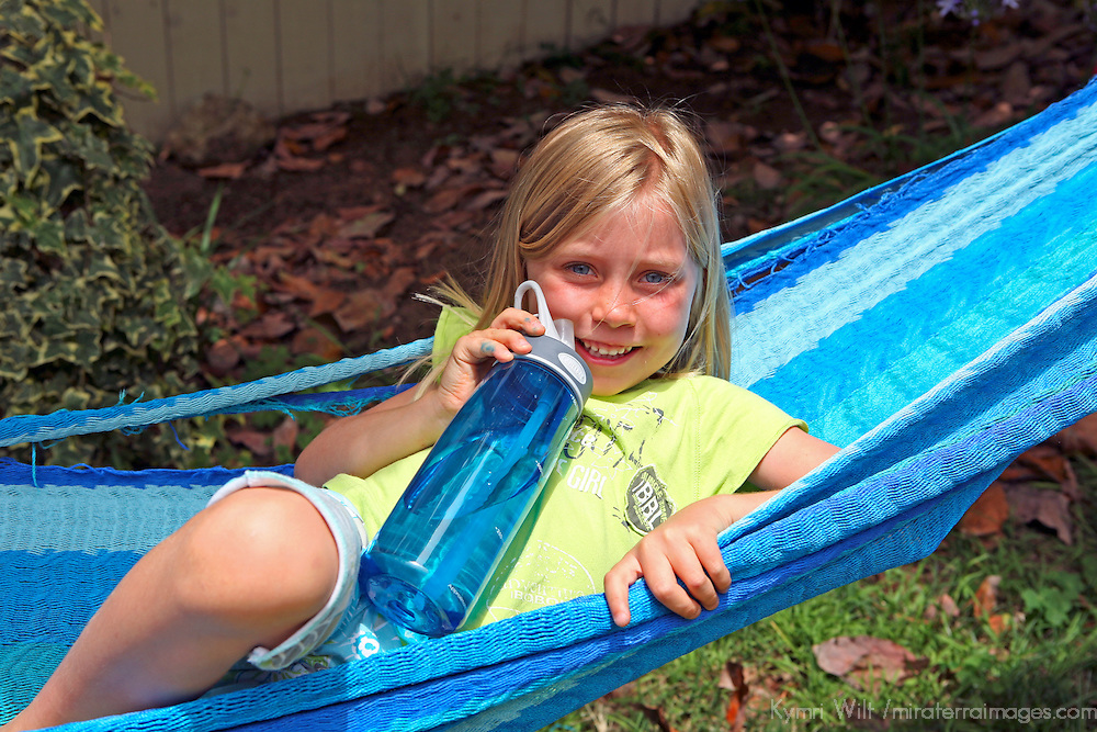 A young girl quenches her thirst with water from a reuasable refillable water bottle as she enjoys outdoor play.