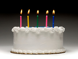 White birthday cake profile on graident background with five colorful lit candles