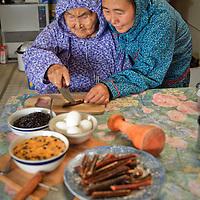 Martha Nicolai holds a salmon strip while Yup'ik Eskimo elder Olinka Nicolai cuts it with her ulu. Kwethuluk. Alaska. The ulu and pestle are used to prepare berries, eggs, salmon strips, and aqutaq.