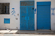 Tunisian Jewish  doors decorated with the symbols of fish and menorahs in the Hara Kebira  neighborhood in Djerba on May 25,2016.In Judaism the fish is a symbol of fertility .Five years after Tunisia's revolution, and a year after three deadly ISIS attacks, the 1,100 Jews in this tiny island community of Djerba say they do not feel threatened living in Tunisia.(Photo by Heidi Levine).