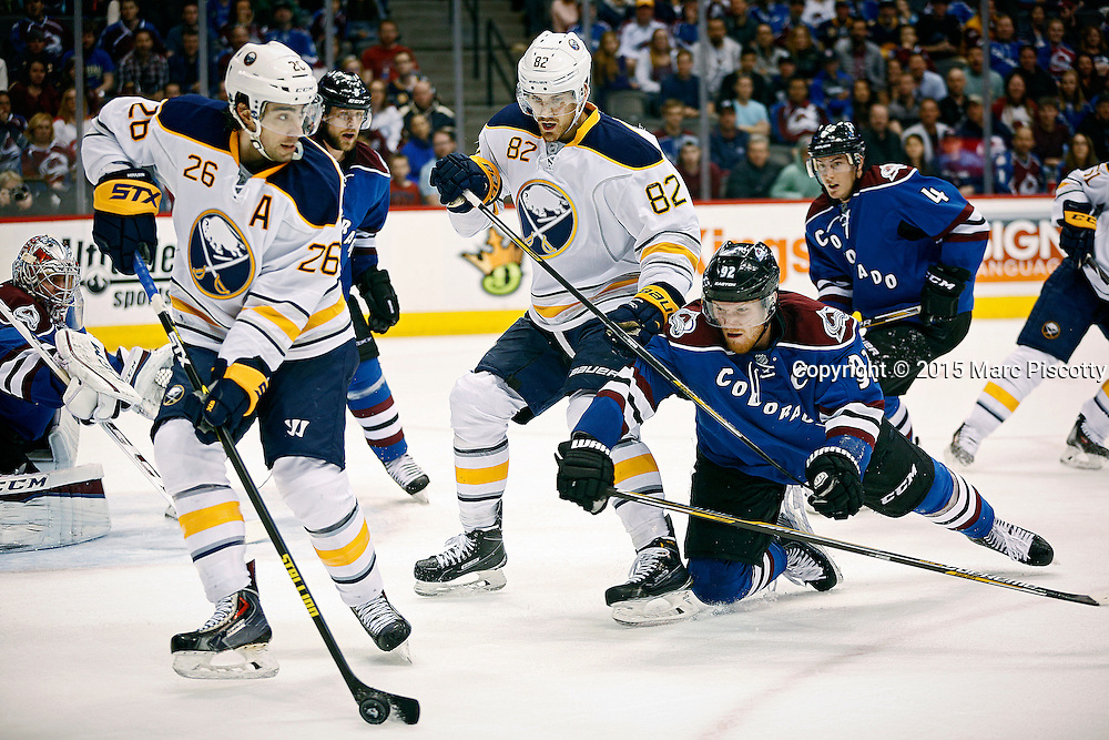 SHOT 3/28/15 9:26:03 PM - The Colorado Avalanche's Gabriel Landeskog #92 dives while attempting to knock the puck away from the Buffalo Sabres' Matt Moulson #26 and Marcus Foligno #82 during their regular season NHL game at the Pepsi Center in Denver, Co. The Avalanche won the game 5-3. (Photo by Marc Piscotty / © 2015)