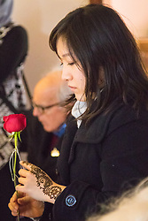 Finsbury Park Mosque, London, February 7th 2016. A woman reflects with a rose she was given by Muslims during a visit to Finsbury Park Mosque as part of a Visit My Mosque initiative by the Muslim Council of Britain to show non-Muslims &ldquo;how Muslims connect to God, connect to communities and to neighbours around them&rdquo;.<br /> . ///FOR LICENCING CONTACT: paul@pauldaveycreative.co.uk TEL:+44 (0) 7966 016 296 or +44 (0) 20 8969 6875. &copy;2015 Paul R Davey. All rights reserved.